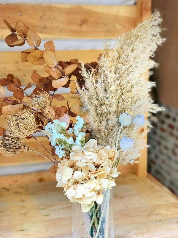 Jarrón con flores preservadas en tonos tostados